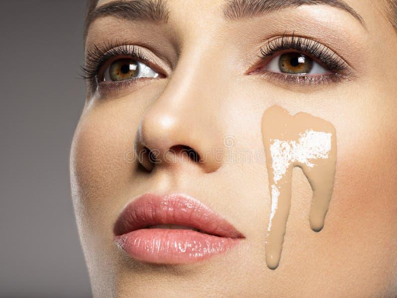 La fundación cosmética líquida del maquillaje está en la cara femenina imagen de archivo