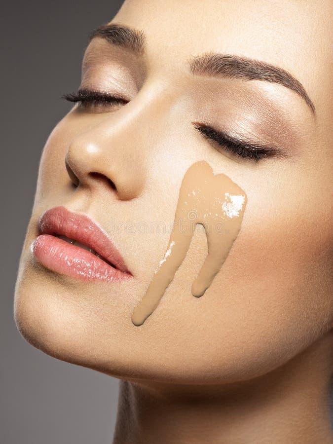 La fundación cosmética líquida del maquillaje está en la cara femenina fotos de archivo