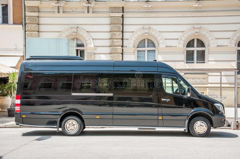 La furgoneta de lujo del servicio de autobús del negro del esprinter de Mercedes Benz parqueó en la calle imágenes de archivo libres de regalías