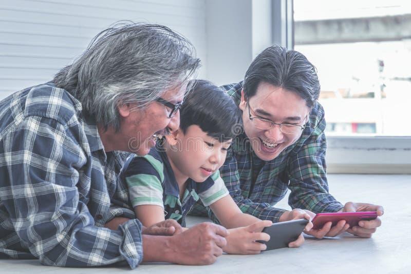 La génération trois de masculin apprend à employer le tohether d'Internet de téléphone portable photographie stock