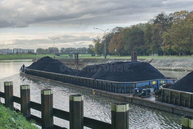 La gabarra fluye a lo largo del río, transporta el carbón a la central eléctrica, reparando las rutas del agua, y transporte verd imágenes de archivo libres de regalías