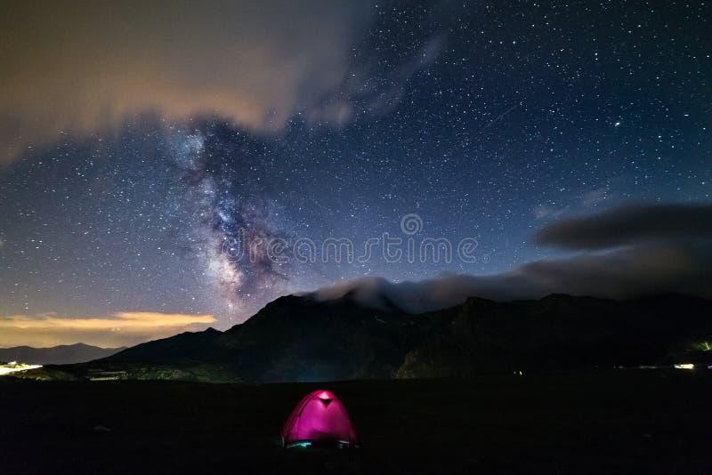 La galassia della Via Lattea stars sopra le alpi, la tenda illuminata di campeggio, il pianeta di Giove e di Marte, la catena mon immagini stock