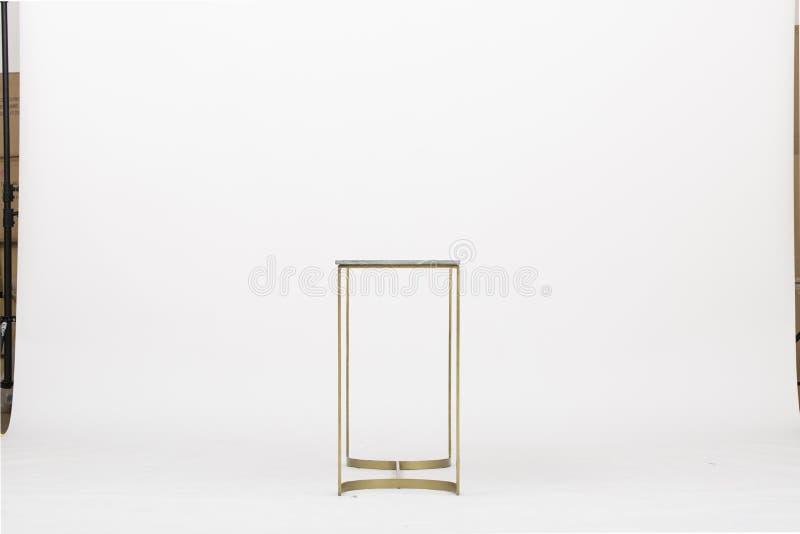 La gamba affusolata d'ottone solida ha smussato il vetro, copertura superiore bianca della foglia di oro della reggenza delle tav fotografia stock