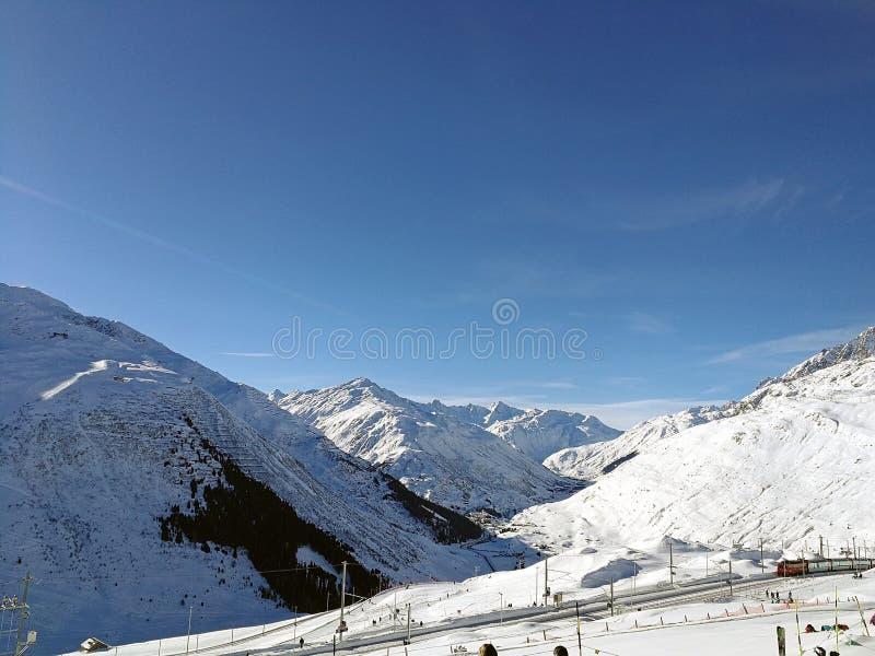 La gare ferroviaire suisse entre la neige a couvert des collines en beau soleil images libres de droits