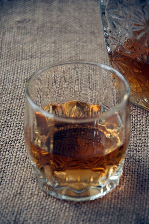 La garrafa y el vidrio del whisky, borbón del whisky en una arpillera, despide el fondo foto de archivo libre de regalías