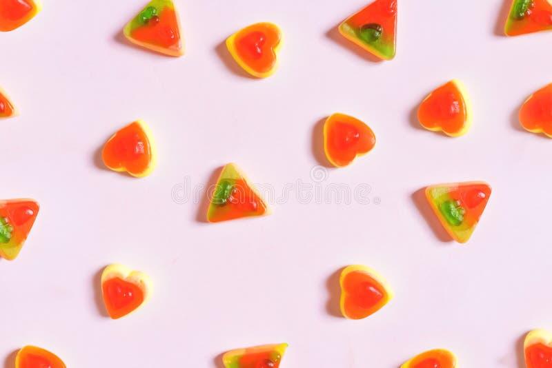 La gelatina, la pizza ed il cuore Colourful modellano sul fondo di rosa pastello fotografia stock
