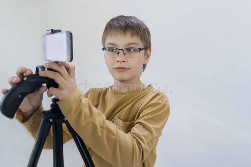 La generación Milenium del colegial se coloca en el muro de cemento en su casa y tira el vídeo para que su canal ponga fotos de archivo