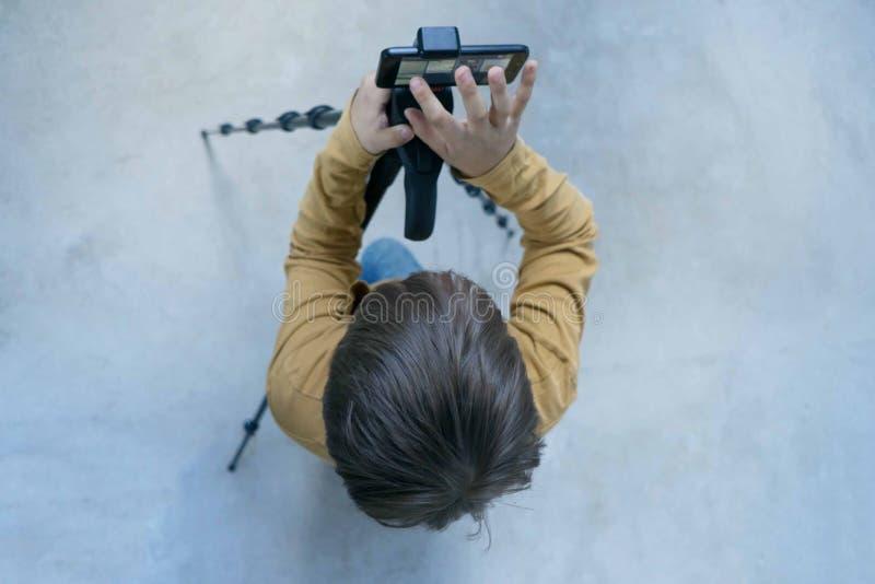 La generaci?n Milenium del colegial se coloca en el muro de cemento en su casa y tira el v?deo para que su canal ponga foto de archivo