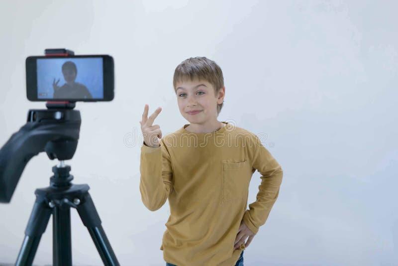 La generazione Milenium dello scolaro sta al muro di cemento nella sua casa e spara il video affinch? il suo canale metta sopra immagini stock