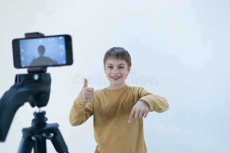 La generazione Milenium dello scolaro sta al muro di cemento nella sua casa e spara il video affinch? il suo canale metta sopra fotografia stock libera da diritti