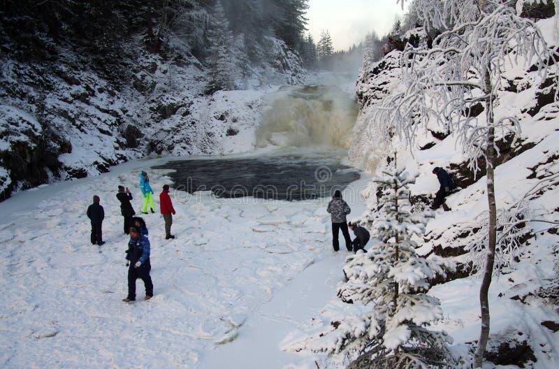 La gente è fotografata sulla cascata Kivach del fondo nel giorno nuvoloso di gennaio La Carelia, Russia fotografia stock
