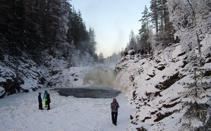 La gente è fotografata sulla cascata Kivach del fondo nel giorno nuvoloso di gennaio La Carelia, Russia fotografia stock libera da diritti