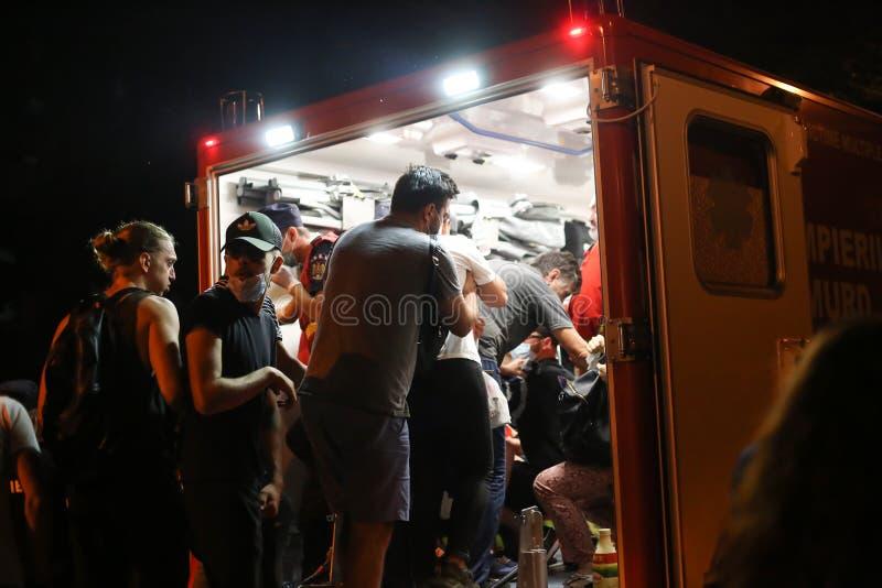 La gente è presa alle ambulanze dopo essere stato ferita durante gli scontri con la polizia di tumulto immagine stock
