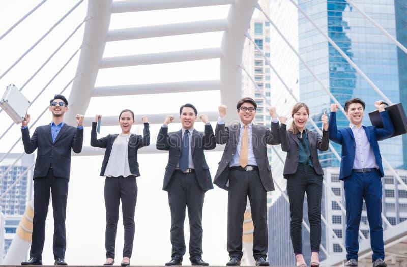 La gente acertada feliz de la unidad de negocio da acertado aumentada con la unidad de negocio acertada del fondo de la ciudad co fotos de archivo libres de regalías