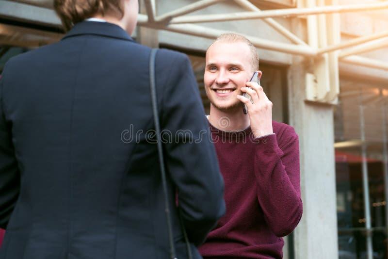 La gente adulta joven de los empresarios tiene reunión de negocios que habla en la calle y que hace llamada de teléfono imagen de archivo