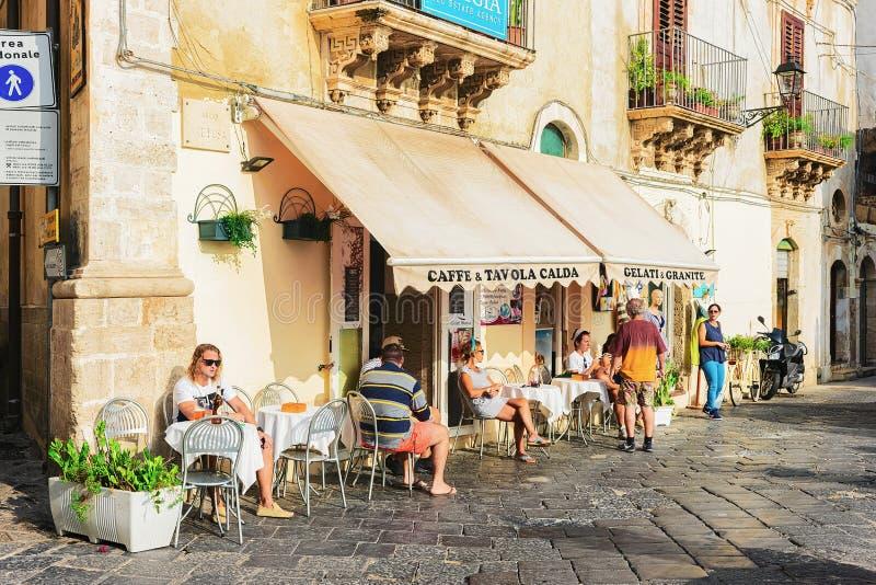 La gente al caffè accogliente della via in Siracusa Sicilia immagini stock libere da diritti