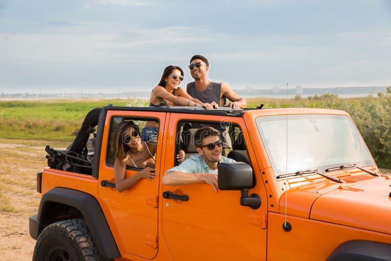 La gente alegre que se divierte esté viajando junta por un coche fotos de archivo