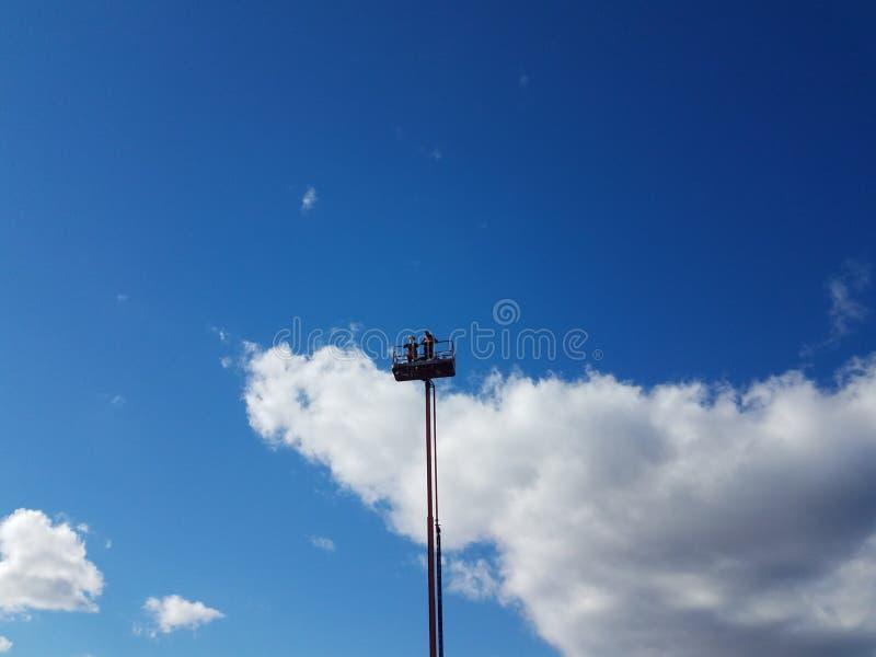La gente alla cima di una raccoglitrice della ciliegia o una torre e un cielo blu con la nuvola immagini stock libere da diritti