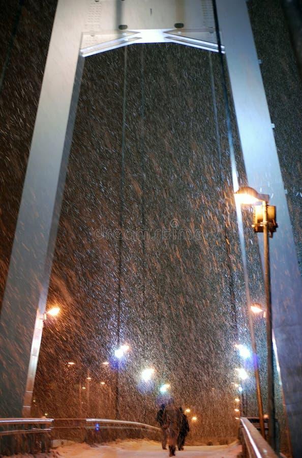 La gente alla notte nell'ambito della bufera di neve pesante fotografia stock libera da diritti