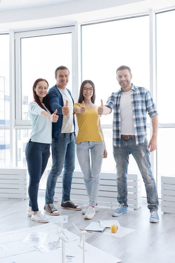 La gente allegra felice che mostra i pollici aumenta i gesti fotografie stock