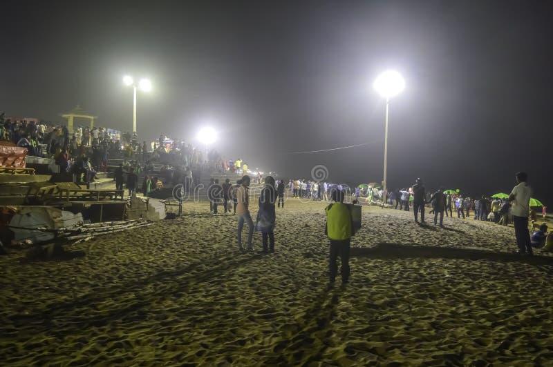 La gente aprieta en la noche después de que puesta del sol en un partido de la playa en las vacaciones de verano - Goa la India foto de archivo