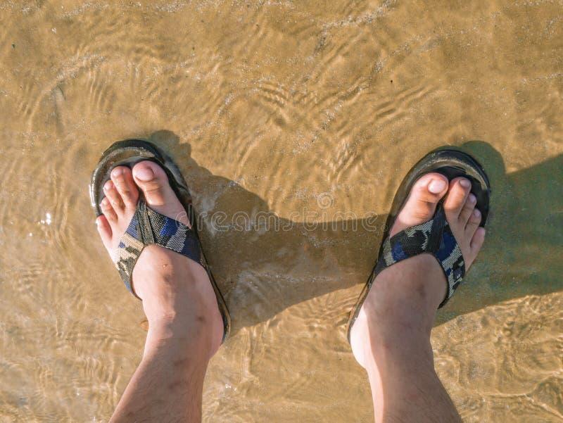 La gente asiática al revés lleva la sandalia en la playa en tiempo de vacaciones fotografía de archivo