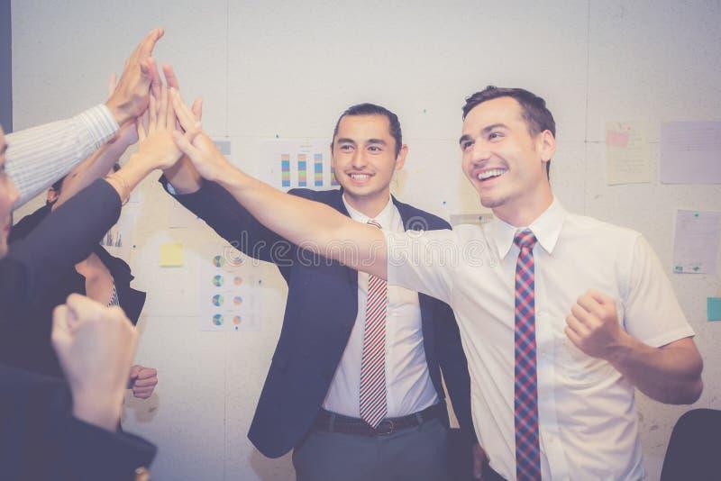 La gente asiática del negocio del grupo combina con el gesto del éxito que da hola cinco en la reunión, acuerdo foto de archivo libre de regalías