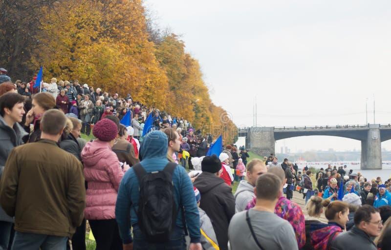 La gente aspetta un tedoforo che porta la fiamma olimpica fotografia stock libera da diritti