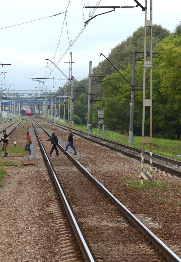 La gente attraversa i binari ferroviari nel posto sbagliato alla stazione della Podlipki-dacia della direzione di Yaroslavl della immagine stock libera da diritti