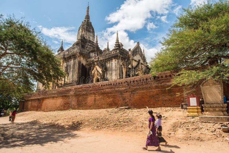 La gente birmana camina pasado el templo en sitios viejos de la arqueología de Bagan, Myanmar de Shwegugyi imágenes de archivo libres de regalías