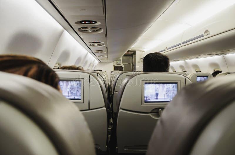 La gente a bordo dell'aereo, sedentesi nei loro sedili guardante TV immagini stock