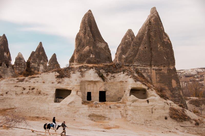La gente camina a caballo contra la perspectiva de roca volcánica y de las cuevas imagenes de archivo