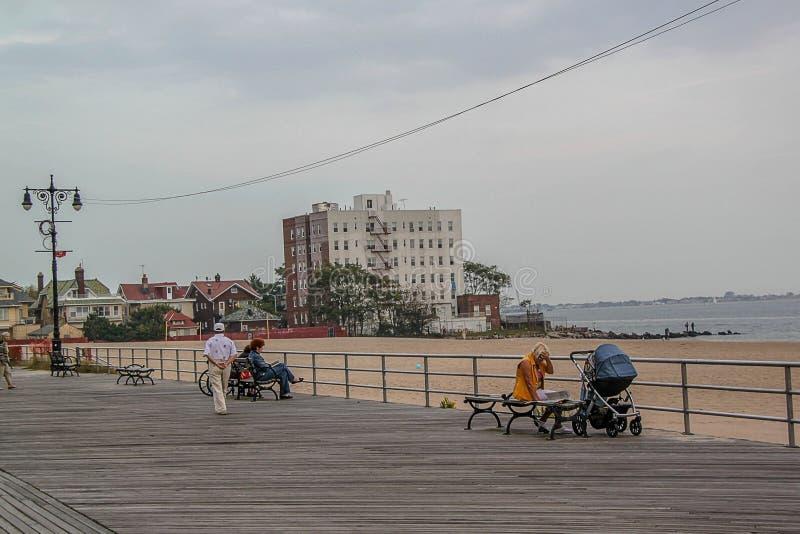 La gente camina a lo largo de la acera y del resto en los bancos a lo largo de los edificios altos contra la perspectiva del mar foto de archivo libre de regalías