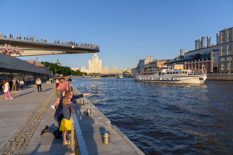 La gente camina a lo largo del terraplén del río de Moscú cerca del parque Zaryadye y del puente de flotación fotos de archivo libres de regalías