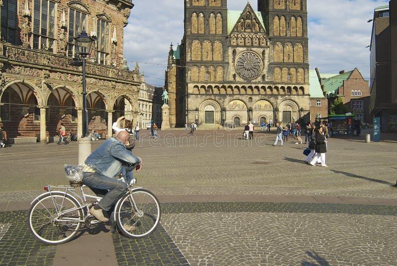 La gente camina por el cuadrado con el ayuntamiento histórico y la catedral en el fondo en Bremen, Alemania foto de archivo