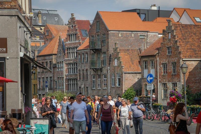 La gente camina a través de la parte central de la ciudad medieval con los cafés, los restaurantes y las tiendas de souvenirs Com imagen de archivo libre de regalías