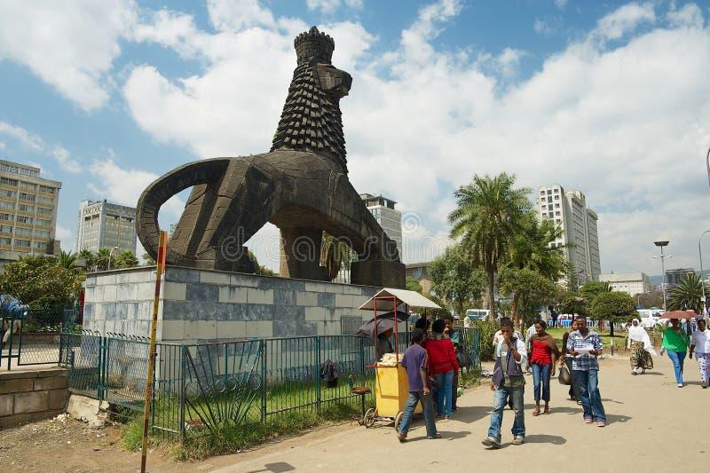 La gente cammina dalla via accanto alla statua iconica del leone di Judah in Addis Ababa, Etiopia fotografia stock
