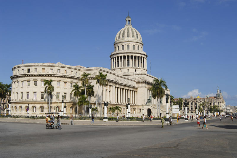 La gente cammina davanti all'edificio di Capitolio a Avana, Cuba immagine stock