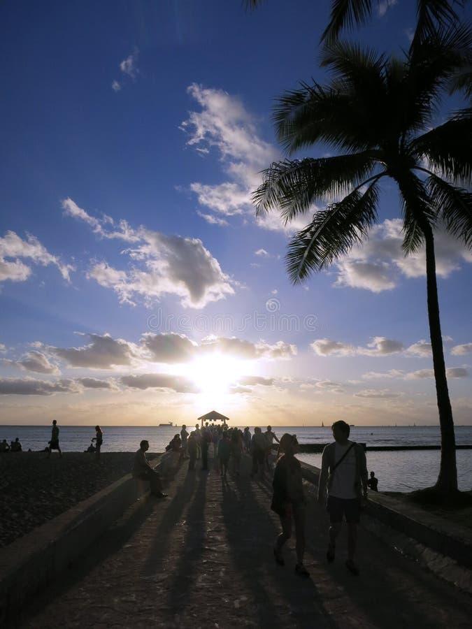 La gente cammina fuori al pilastro per guardare il tramonto in Waikiki immagini stock