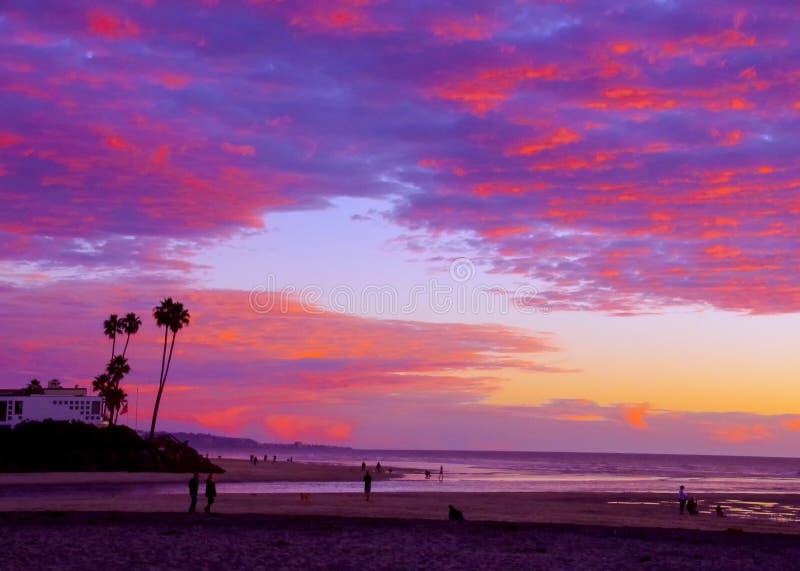 La gente cammina lungo la spiaggia con l'entrata di marea che gode di un tramonto glorioso, Del Mar, la California immagini stock
