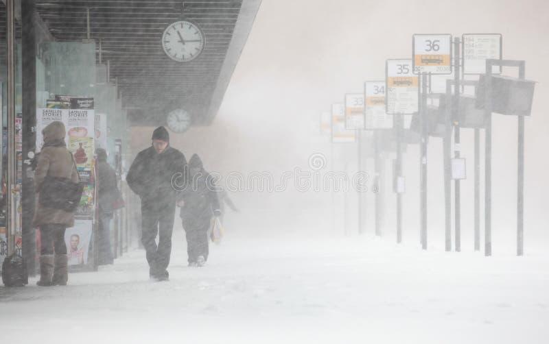 La gente cammina sotto forte nevicata inattesa immagini stock