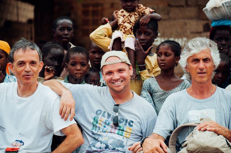 La gente caucasica bianca e la gente dell'africano nero godono della vita in un villaggio rurale immagini stock libere da diritti