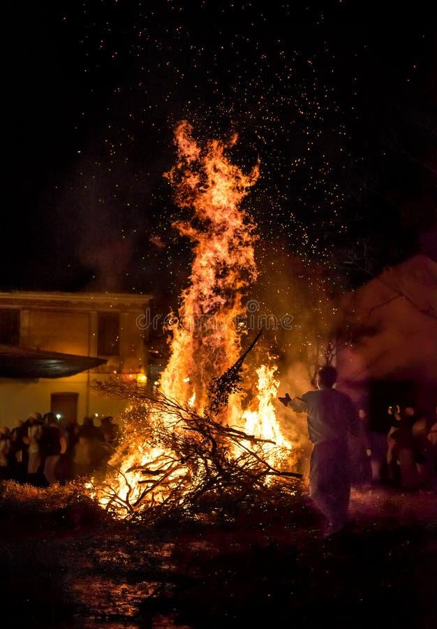 La gente celebra il ` s EVE di St John intorno ad un falò in una villa greca immagine stock libera da diritti