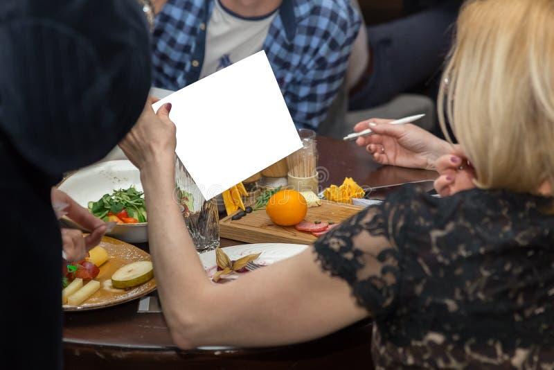 la gente cenando insieme mentre sedendosi alla tavola di legno Mano femminile che tiene Libro Bianco immagine stock libera da diritti