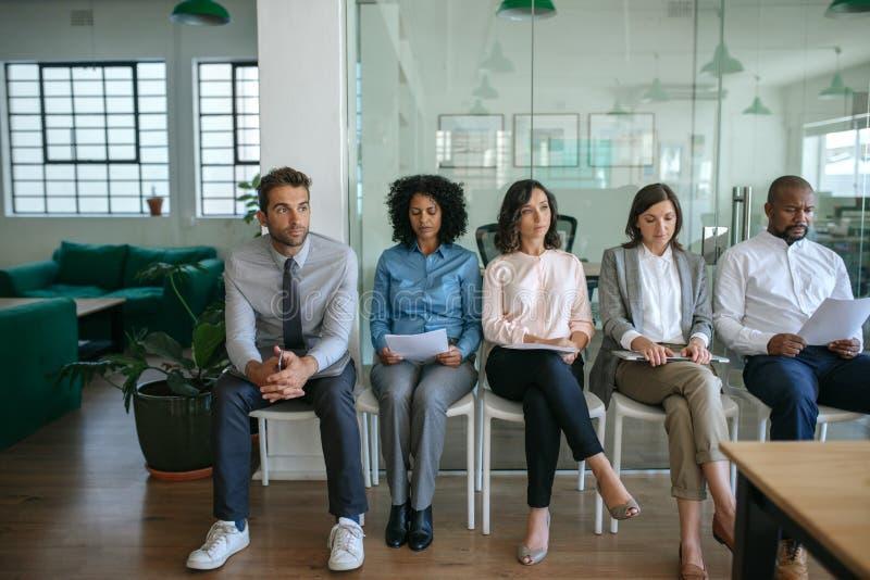 La gente che aspetta le loro interviste di lavoro in un ufficio fotografia stock