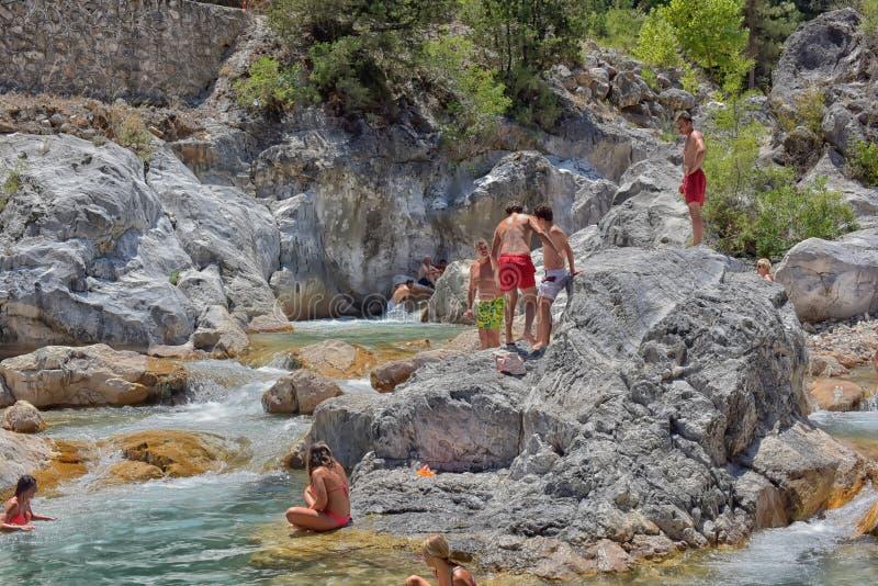 La gente che bagna in un fiume della montagna immagine stock