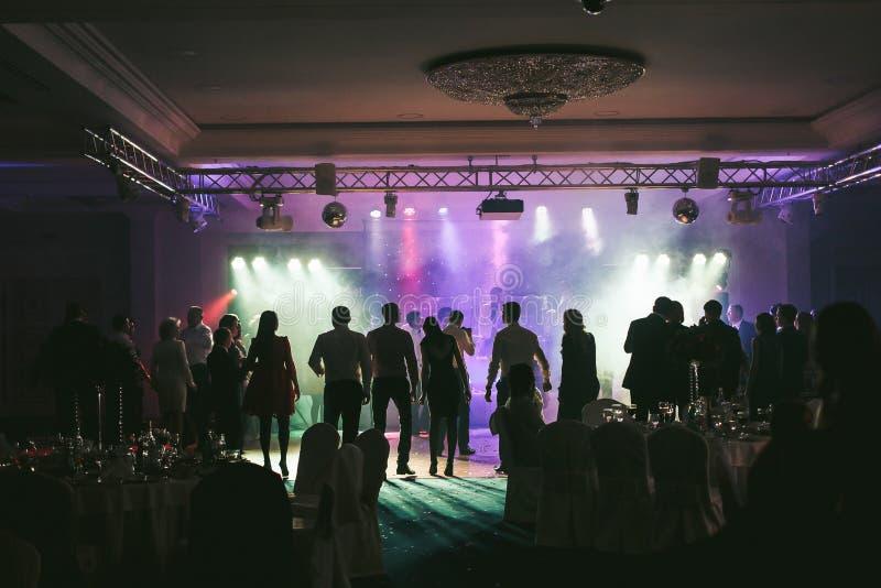 La gente che balla alle luci al neon durante la festa nuziale immagine stock libera da diritti