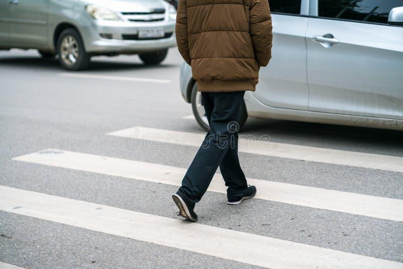 La gente che cammina attraverso una via mentre le automobili continuano correre sulla via a Hanoi, Vietnam closeup immagine stock libera da diritti