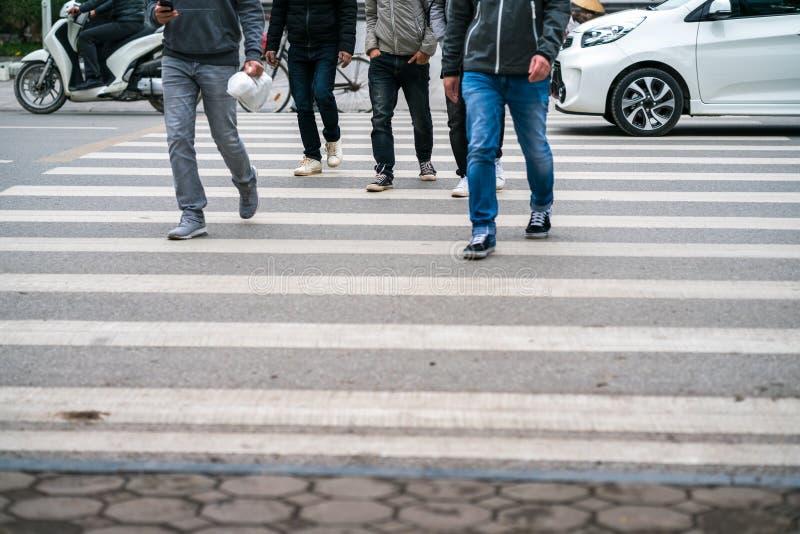 La gente che cammina attraverso una via mentre le automobili continuano correre sulla via a Hanoi, Vietnam closeup immagine stock