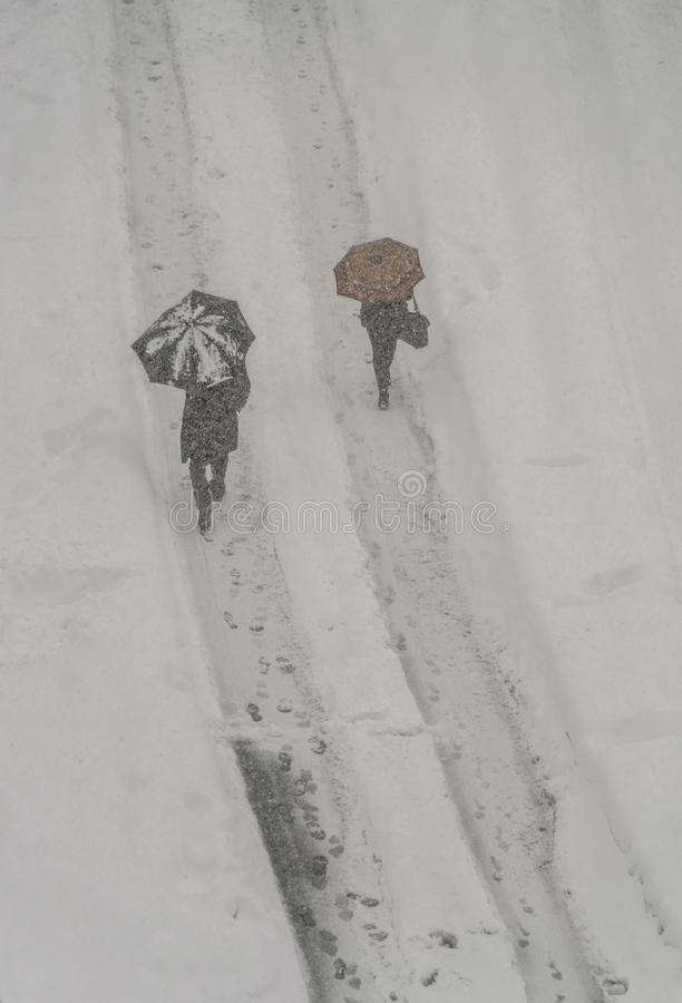 La gente che cammina con gli ombrelli in un giorno nevoso immagini stock